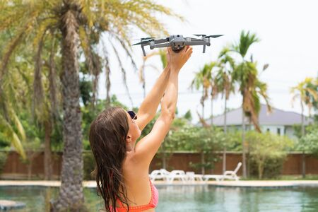 Foto de female launches a drone for flight, with which you can take photos and videos, near the swimming pool and palm trees, side view. - Imagen libre de derechos