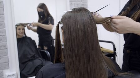 Photo for Cute girl with long brunette hair hairdresser doing hair lamination in a beauty salon. concept of hair care treatment. - Royalty Free Image