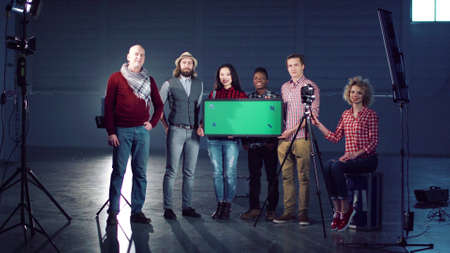 Cheerful film diverse team posing with a chromakey board.