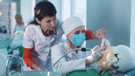 Foto de Dentistry student or hygienist practicing on a dummy at a medical school as a qualified teacher demonstrates the technique to her from behind - Imagen libre de derechos