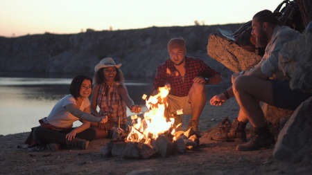 Photo pour Group of multiracial people sitting around campfire grilling marshmallows and having fun on coast. - image libre de droit