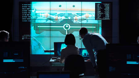 Foto de Back view of man and woman in space flight control center. Docking of space modules. - Imagen libre de derechos