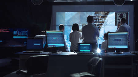 Foto de Back view of people working and managing flight in mission control center. Elements of this image furnished by NASA. - Imagen libre de derechos