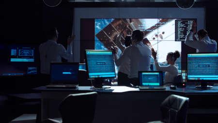 Foto de Group of supervisors celebrating docking of spaceship in dark room of mission control center. - Imagen libre de derechos