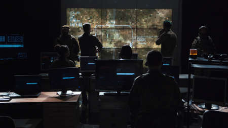 Foto de Group of soldiers or spies in dark room with large monitors and advanced satellite communication technology launching a missle. Includes flashing yellow light. - Imagen libre de derechos