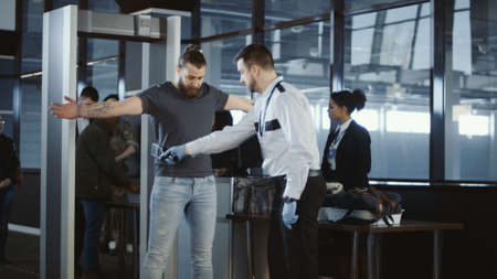 Foto de Security agent at an airport check-in gate patting down a bearded casual male passenger with outstretched arms after he passes through the metal detector scanner in the departures hall. - Imagen libre de derechos