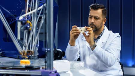 Foto de Serious man in laboratory exploring three-dimensional cranium fragment working for engineering medicine. - Imagen libre de derechos