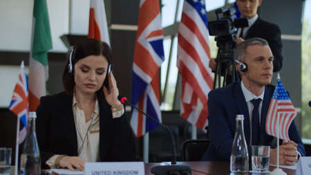 Foto de Formal international politicians in headphones sitting at table on summit and listening to speech translation in headphones - Imagen libre de derechos