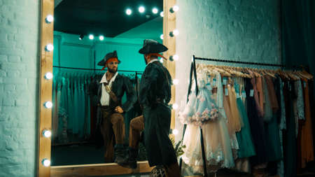 Foto de Back view of man wearing costume of pirate and standing in front of mirror in dressing room practicing scene from performance - Imagen libre de derechos