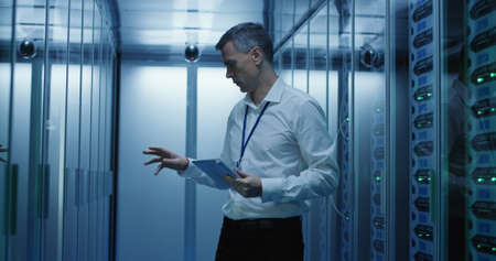 Foto de Medium shot of technician working on a tablet in a data center full of rack servers running diagnostics and maintenance on the system - Imagen libre de derechos