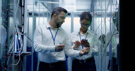 Foto de Medium shot of a manager performing an inspection while working in a data center inbetween rows of server racks - Imagen libre de derechos