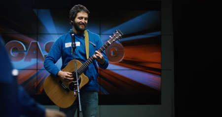 Foto de Medium shot of young man singing and playing guitar at casting - Imagen libre de derechos