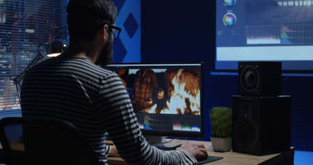 Foto de Medium shot of young man sitting back and editing video and making color grading inside a modern video studio - Imagen libre de derechos