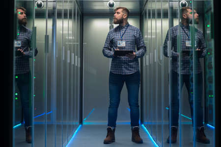 Photo pour Portrait of adult bearded man and woman standing in corridor of server room in data center smiling at camera - image libre de droit