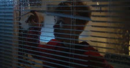 Photo for Medium shot of a boy opening blinds to watch the rainfall through the window - Royalty Free Image
