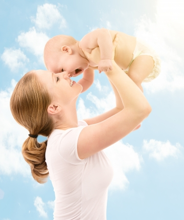 Photo for happy family. Mother throws up and kissing baby in the sky in nature - Royalty Free Image