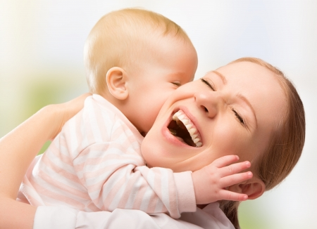 Foto de Happy cheerful family. Mother and baby kissing, laughing and hugging - Imagen libre de derechos