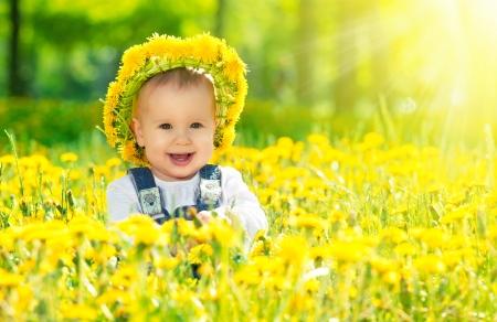 Foto de Beautiful happy little baby girl in a wreath  on a  meadow with yellow flowers dandelions on the nature in the park - Imagen libre de derechos