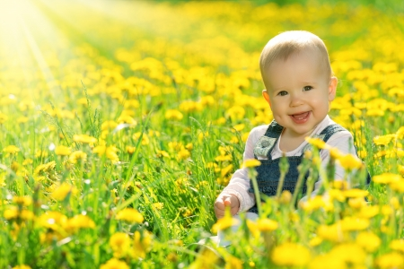 Foto de Beautiful happy little baby girl sitting on a green meadow with yellow flowers dandelions on the nature in the park - Imagen libre de derechos