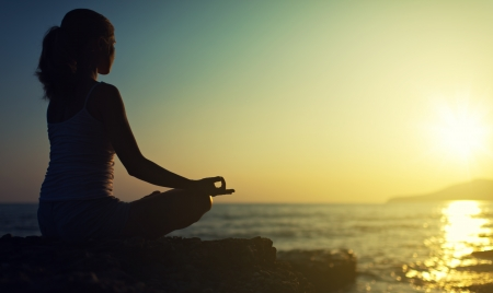 Photo pour yoga outdoors. silhouette of a woman sitting in a lotus position on the beach at sunset - image libre de droit