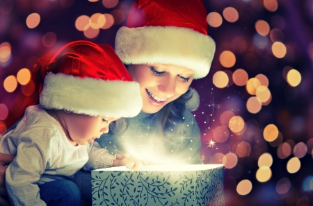 Photo for Christmas magic gift box and a woman happy family mother and Child baby - Royalty Free Image