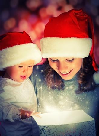 Foto de Christmas magic gift box and a woman happy family mother and Child baby - Imagen libre de derechos