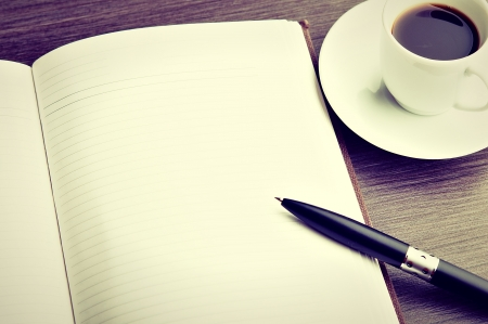 Foto de Open a blank white notebook, pen and cup of coffee on the desk - Imagen libre de derechos