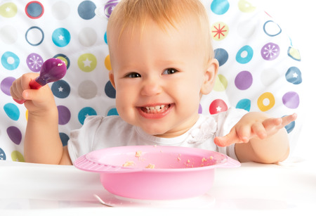 Photo pour cheerful happy baby child eats itself with a spoon - image libre de droit