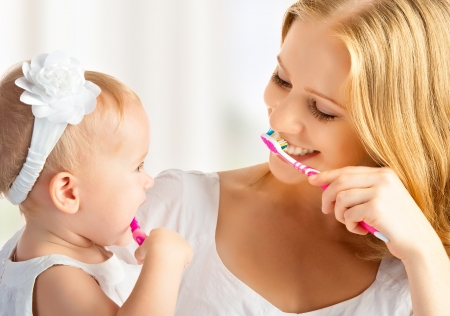 Photo pour happy family and health. mother and daughter baby girl brushing their teeth together - image libre de droit