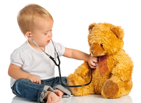 Foto de baby plays in doctor toy bear and stethoscope - Imagen libre de derechos