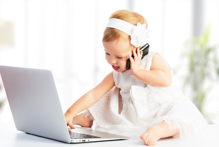 Photo pour baby girl with computer laptop and mobile phone - image libre de droit