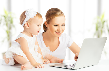 Photo for Mom and baby with laptop computer working from home - Royalty Free Image