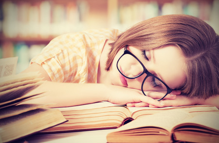 Photo pour tired student girl with glasses sleeping on the books in the library - image libre de droit