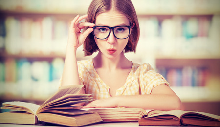 Foto de funny crazy  girl student with glasses reading books in the library - Imagen libre de derechos