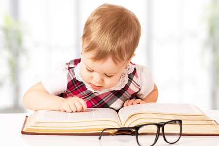 Photo pour Happy funny baby girl in glasses reading a book in a library - image libre de droit
