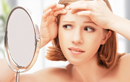Photo pour young beautiful healthy woman  frightened saw in the mirror acne and wrinkles - image libre de droit