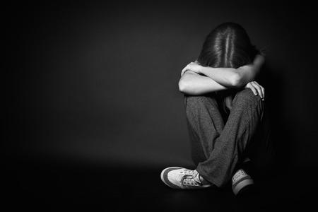 Foto de sad woman in depression and despair crying on black dark background - Imagen libre de derechos