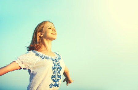 Foto de happy young woman open her arms to the sky and enjoying life - Imagen libre de derechos