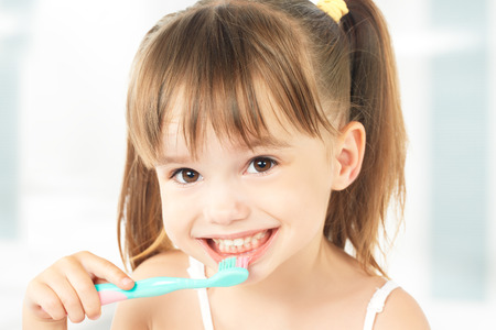 Foto per dental hygiene. happy little girl brushing her teeth - Immagine Royalty Free