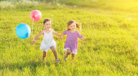 Photo pour happy kids twin sisters running around laughing and playing with balloons in the meadow in summer - image libre de droit