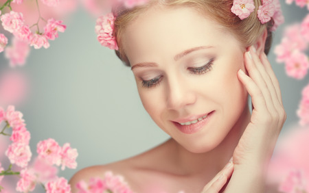 Photo pour Beauty face of the young beautiful woman with pink flowers in her hair - image libre de droit