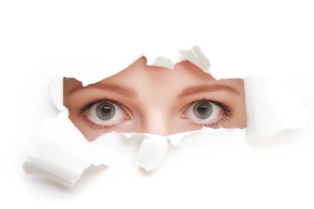 Photo for eyes of a young curious woman peeking through a  hole torn in white paper poster - Royalty Free Image