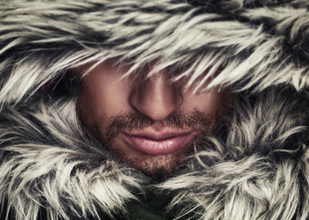 Photo for brutal face of a man with beard bristles and hooded winter - Royalty Free Image