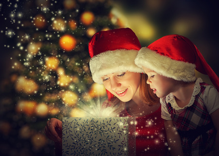 Photo for Christmas magic gift box and a woman happy family mother and daughter baby girl - Royalty Free Image