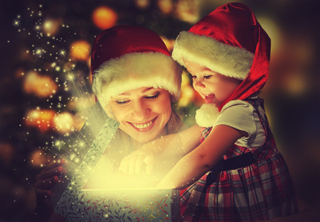 Foto de Christmas magic gift box and a woman happy family mother and daughter baby girl - Imagen libre de derechos