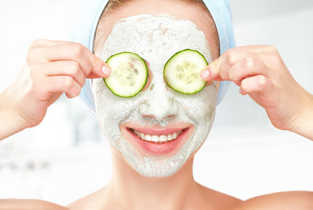 Photo for Funny young girl with a mask for skin face and cucumbers on eyes - Royalty Free Image