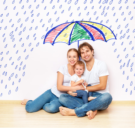 Foto de concept: the social protection of the family. family took refuge from the miseries and rain under an umbrella - Imagen libre de derechos