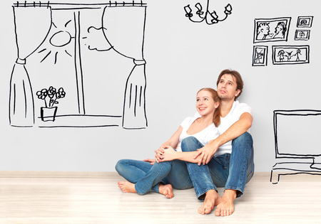 Foto de Concept family: Happy couple in the new apartment dream and plan interior - Imagen libre de derechos