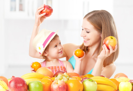 Photo for happy family mother and daughter little girl, eat healthy vegetarian food, lots of fruit - Royalty Free Image