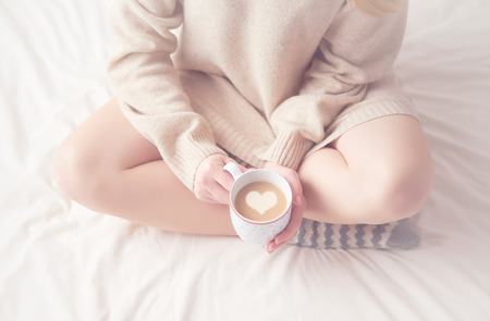 Foto de legs of girl warm woolen socks and a cup of coffee warming, winter morning at home in bed - Imagen libre de derechos